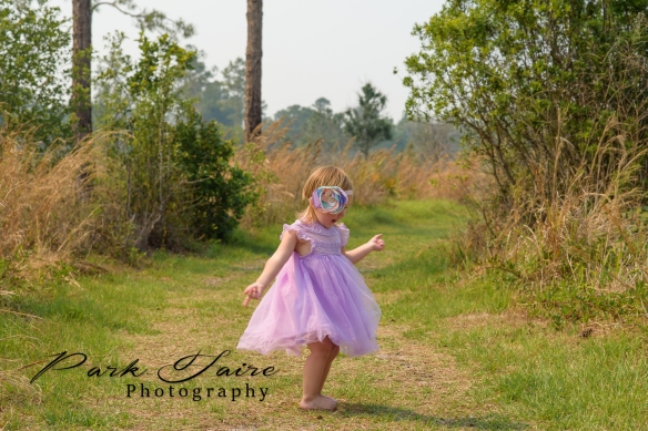 lakeland child photographer toddler girl purple dress pink teal flower headband 2 year old tall grass dance twirl